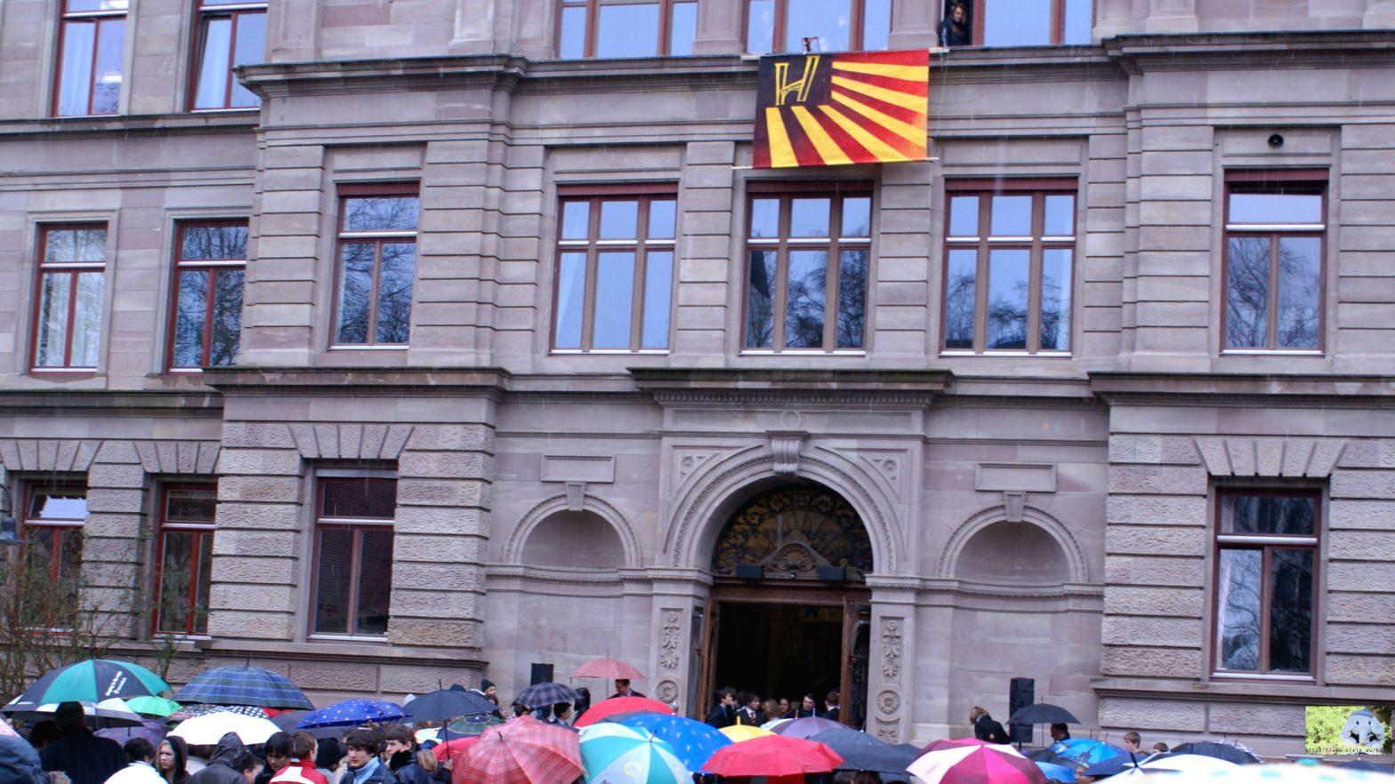 Schulgebäude mit Fahne Humbolei, und Schülern unter Regenschirmen