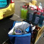 Einkaufswagen abladen, in Kühltasche und Kisten verpacken vorm Einladen