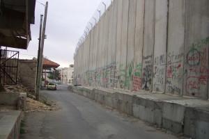 Die Mauer in Bethlehem, Palästina, Häuser, ein Auto, alles wirkt winzig neben dieser Mauer