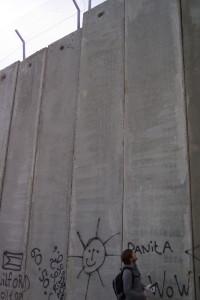 Die Mauer in Bethlehem, Palästina, die lachende, gemalte Sonne wirkt groß neben einem Menschen, doch die Mauer bleibt riesig und trist.