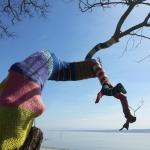 mit bunter Wolle verschönert, Baum ohne Blätter mit Blick auf den See