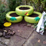 mit Blumenerde gefüllt - Gartendeko Reifenfrosch bepflanzt